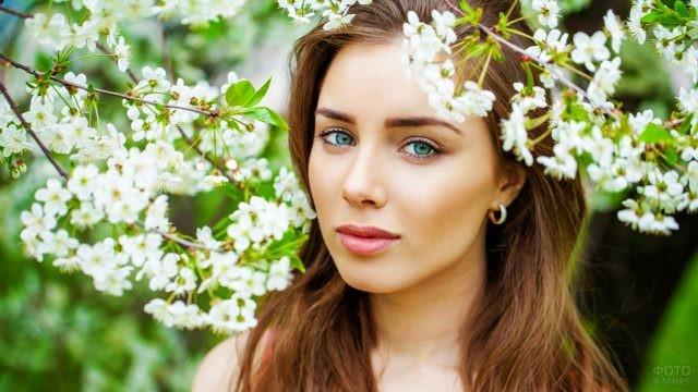 Зеленоглазая девушка под цветущей яблоней